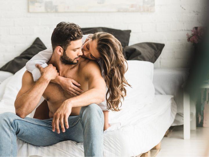 la femme a serré l'homme dans ses bras alors qu'il était assis sur le lit et l'a embrassé sur la joue