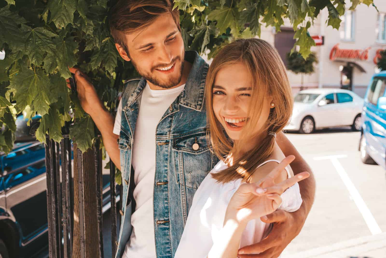 Sourire belle fille et son beau petit ami posant dans la rue près de larbre