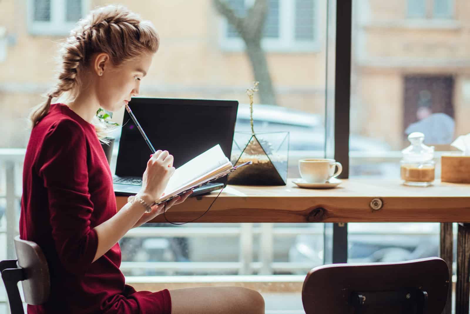 Une femme assise à une table dans une robe bordeaux et écrit