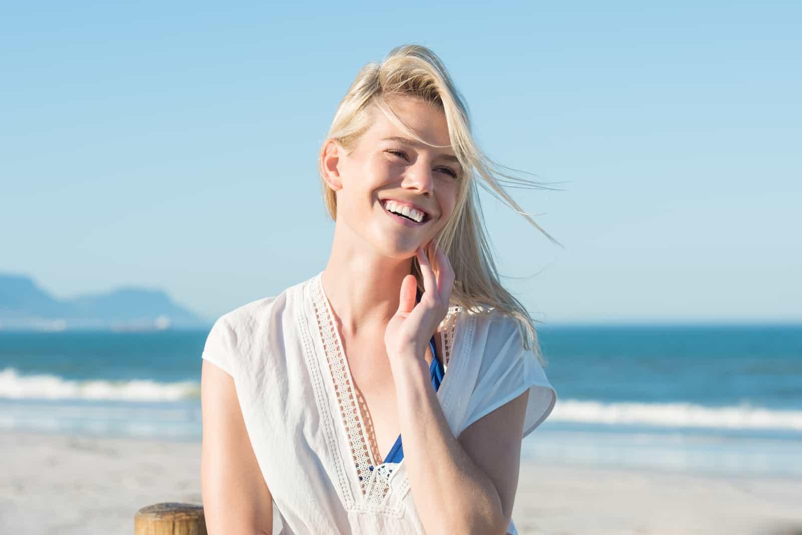 Une femme aux longs cheveux blonds rit en se tenant debout sur la plage