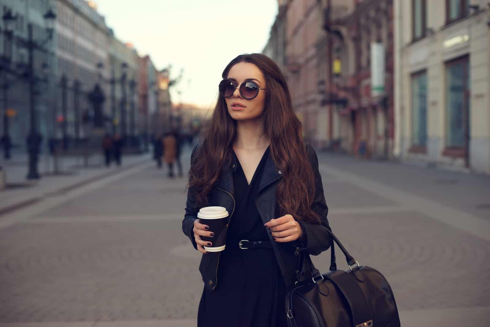 Une femme aux longs cheveux bruns se tient avec du café à la main