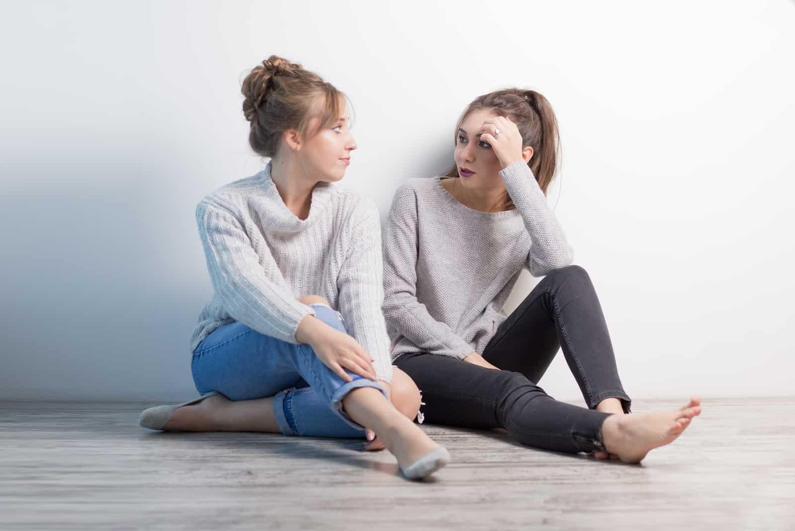 deux femmes s'assoient sur le sol et parlent