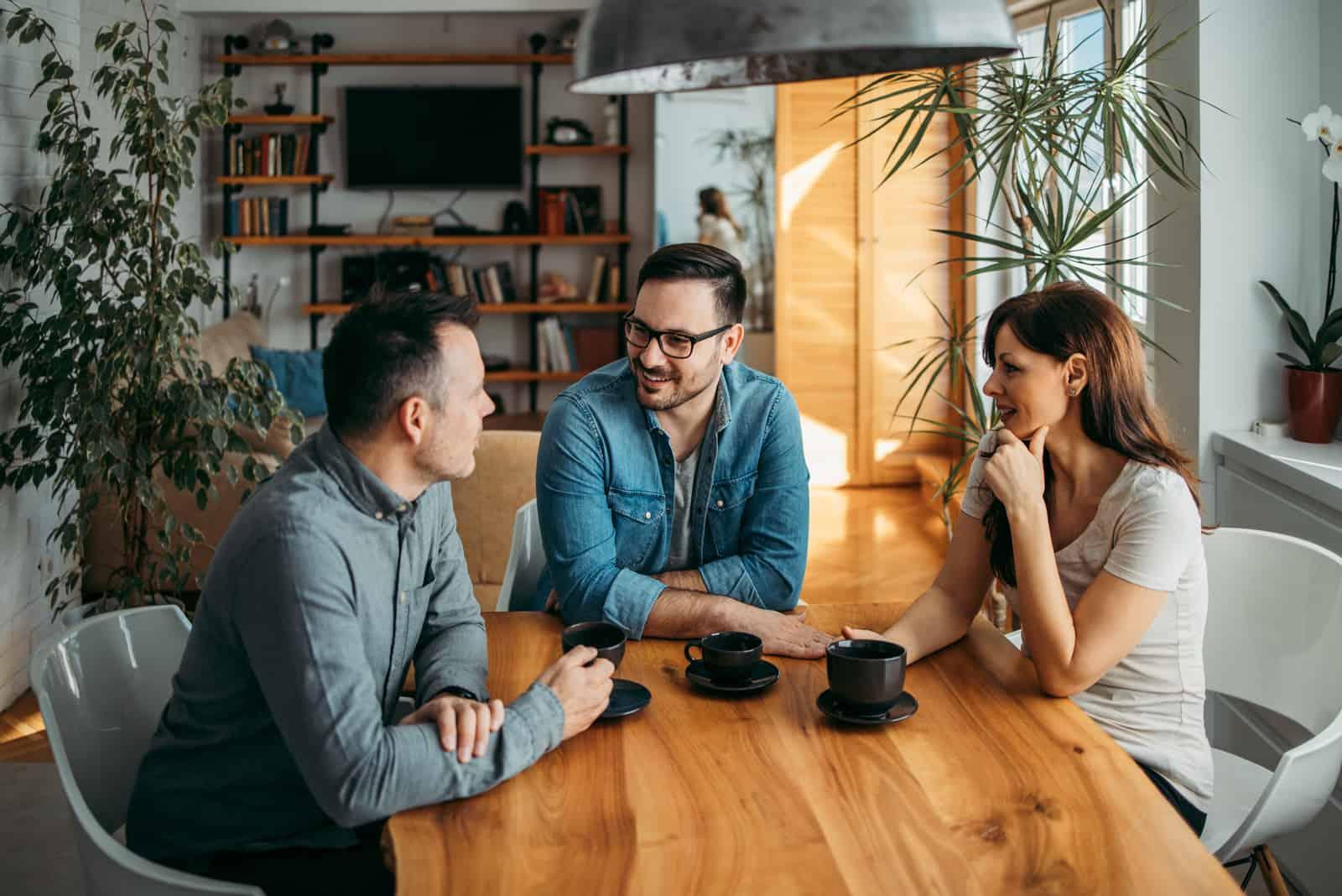 deux hommes et une femme sont assis en train de boire du café et de parler