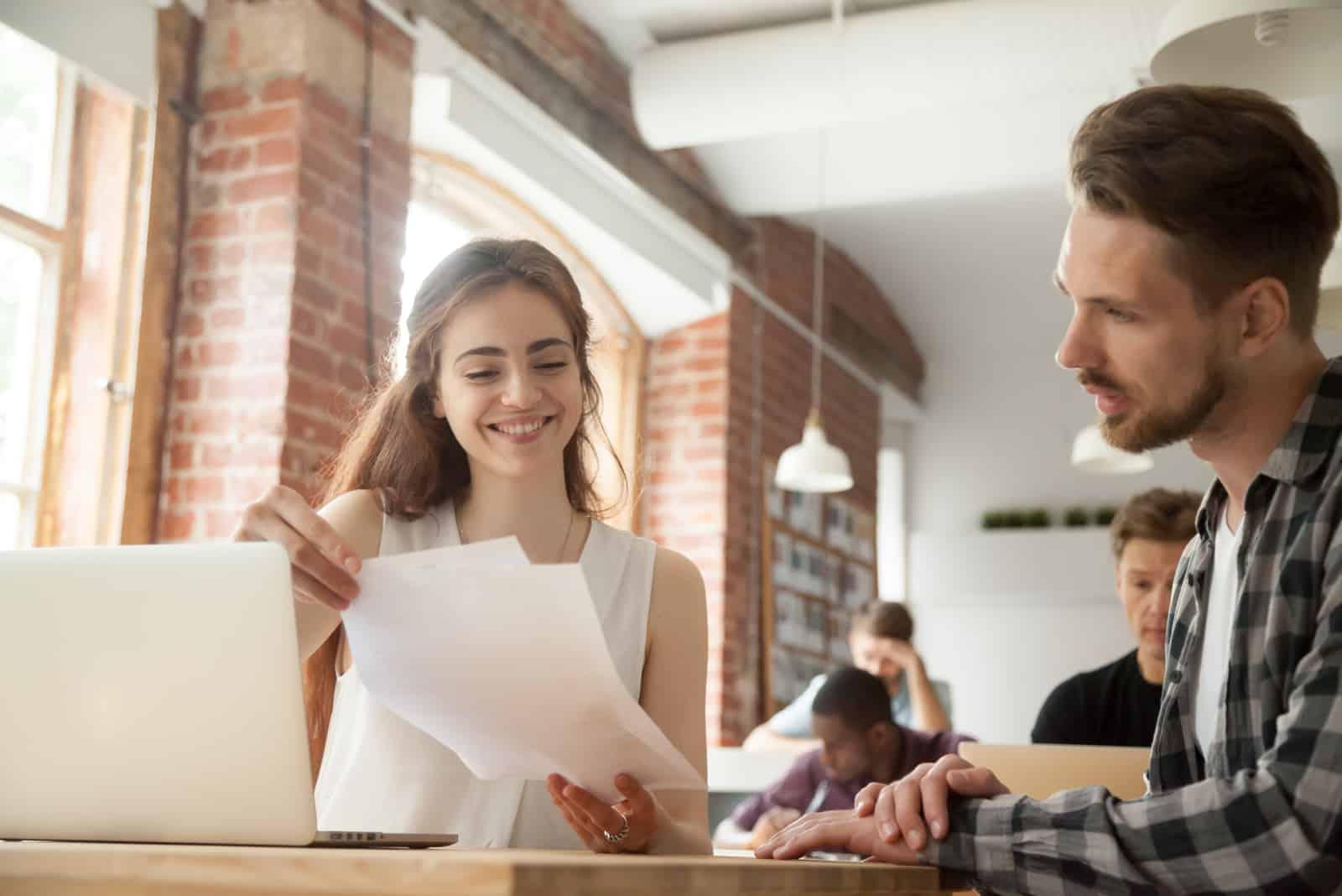 employé de femme souriante aidant le mentorat jeune homme stagiaire