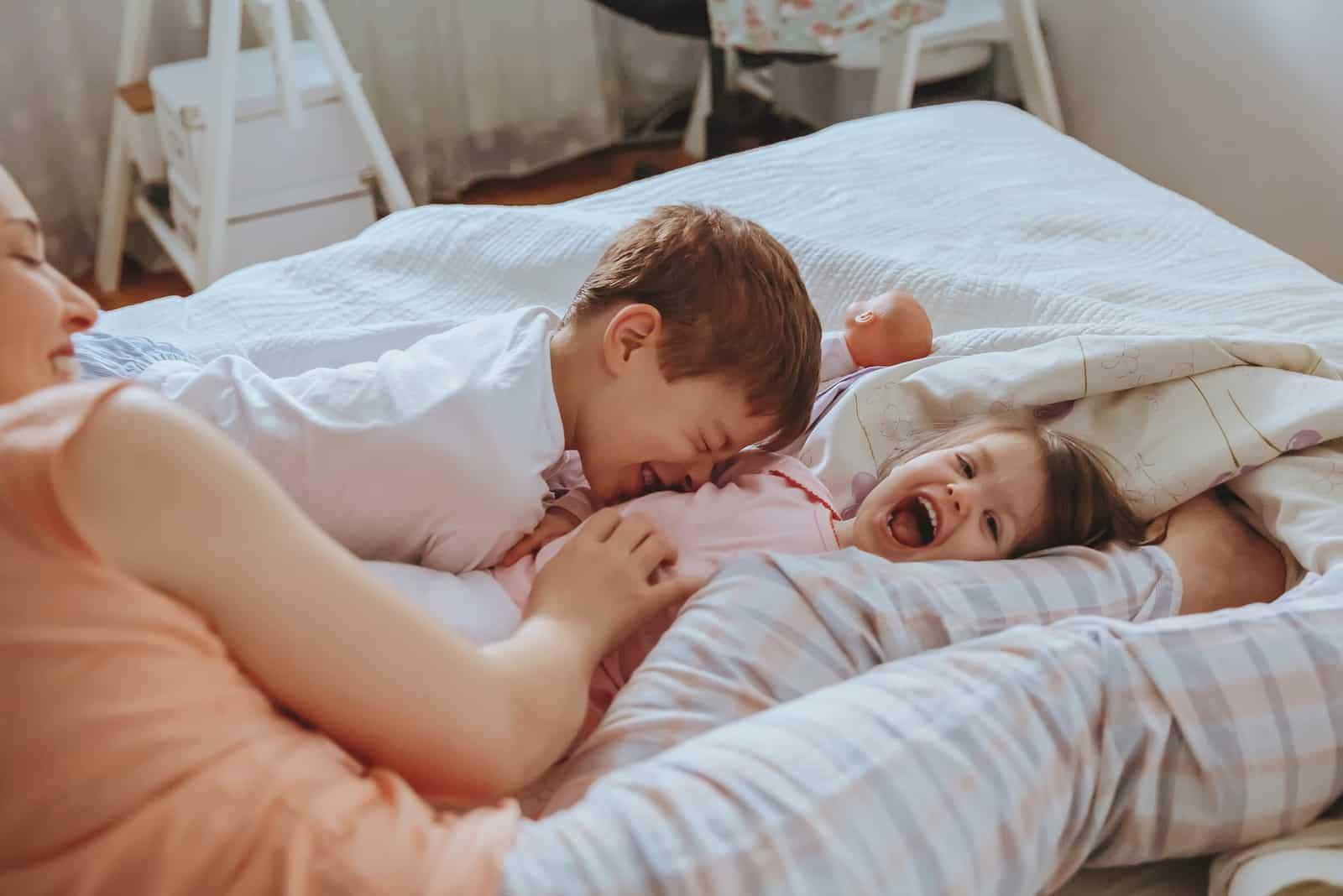famille heureuse jouant sur le lit dans une matinée détendue