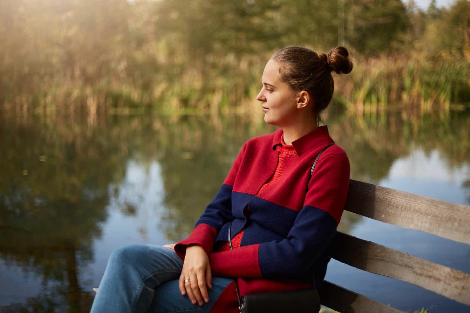 femme pensive assis sur un banc en bois