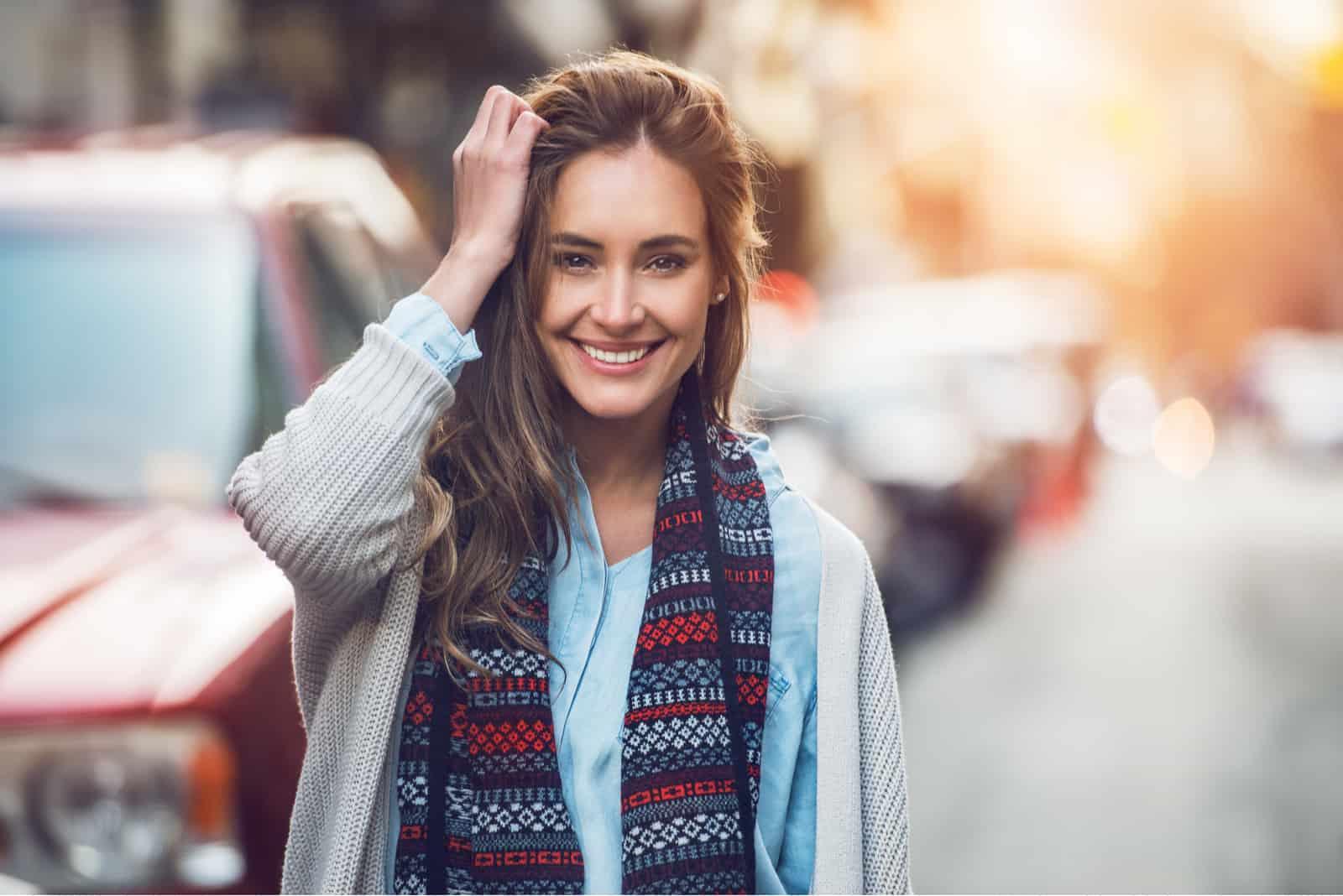 femme souriante, à, dents, sourire, dehors, et, marche, sur, rue ville