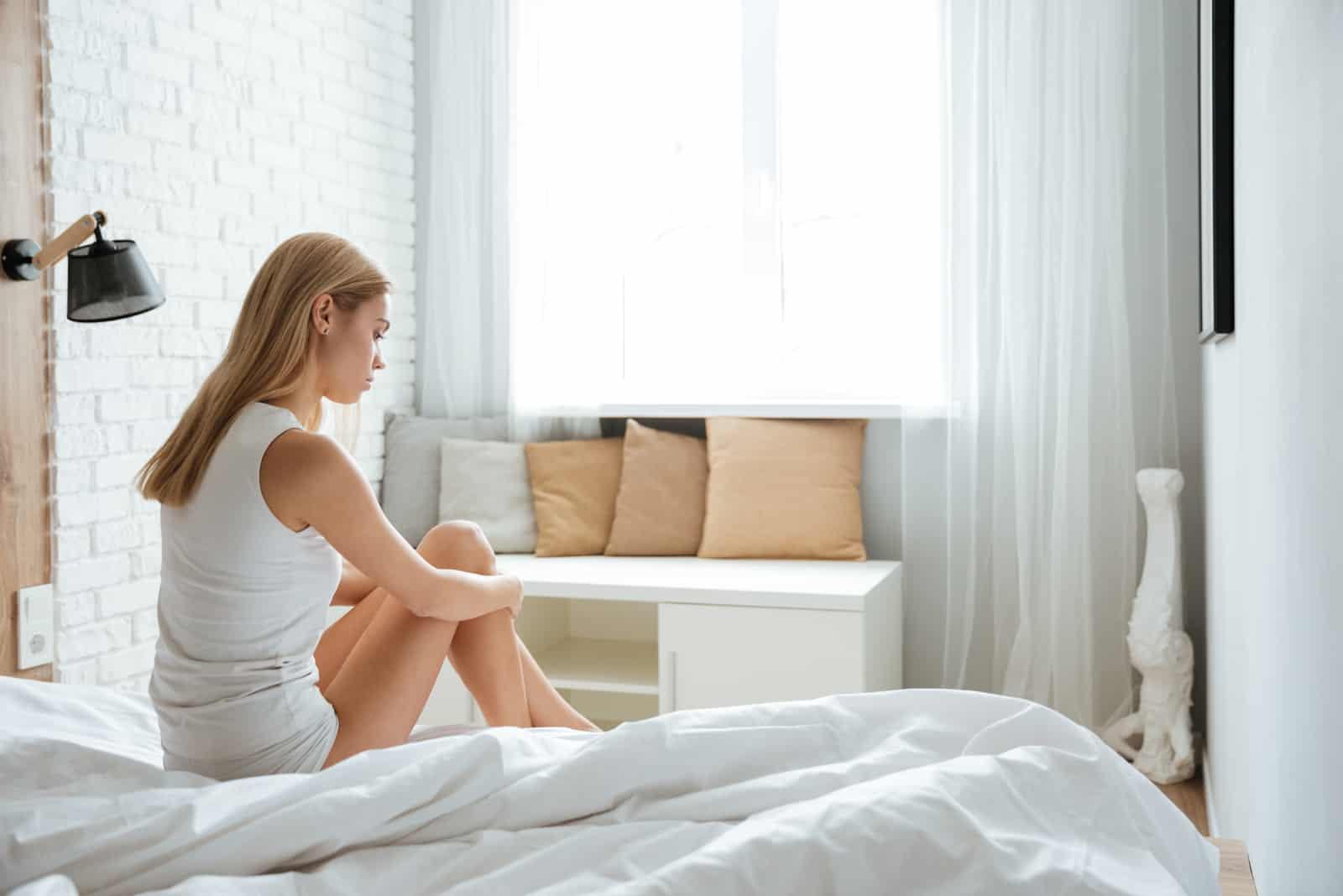 femme triste assise sur le lit