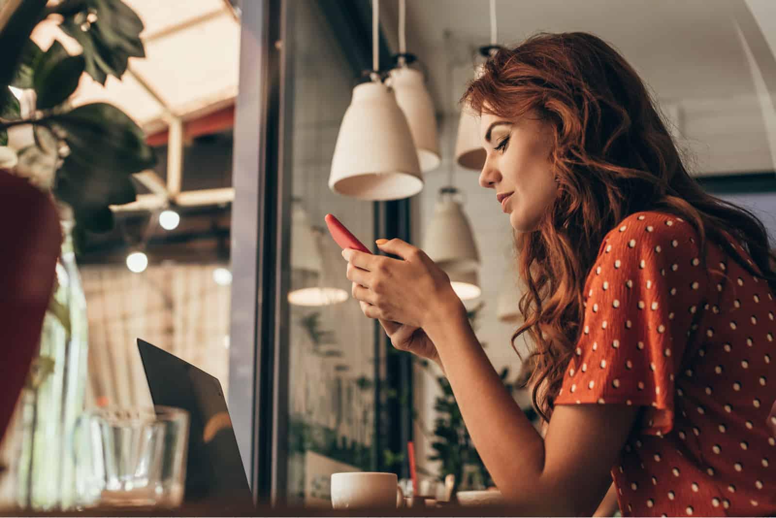 jeune femme, utilisation, smartphone, table, à, ordinateur portable, dans, café