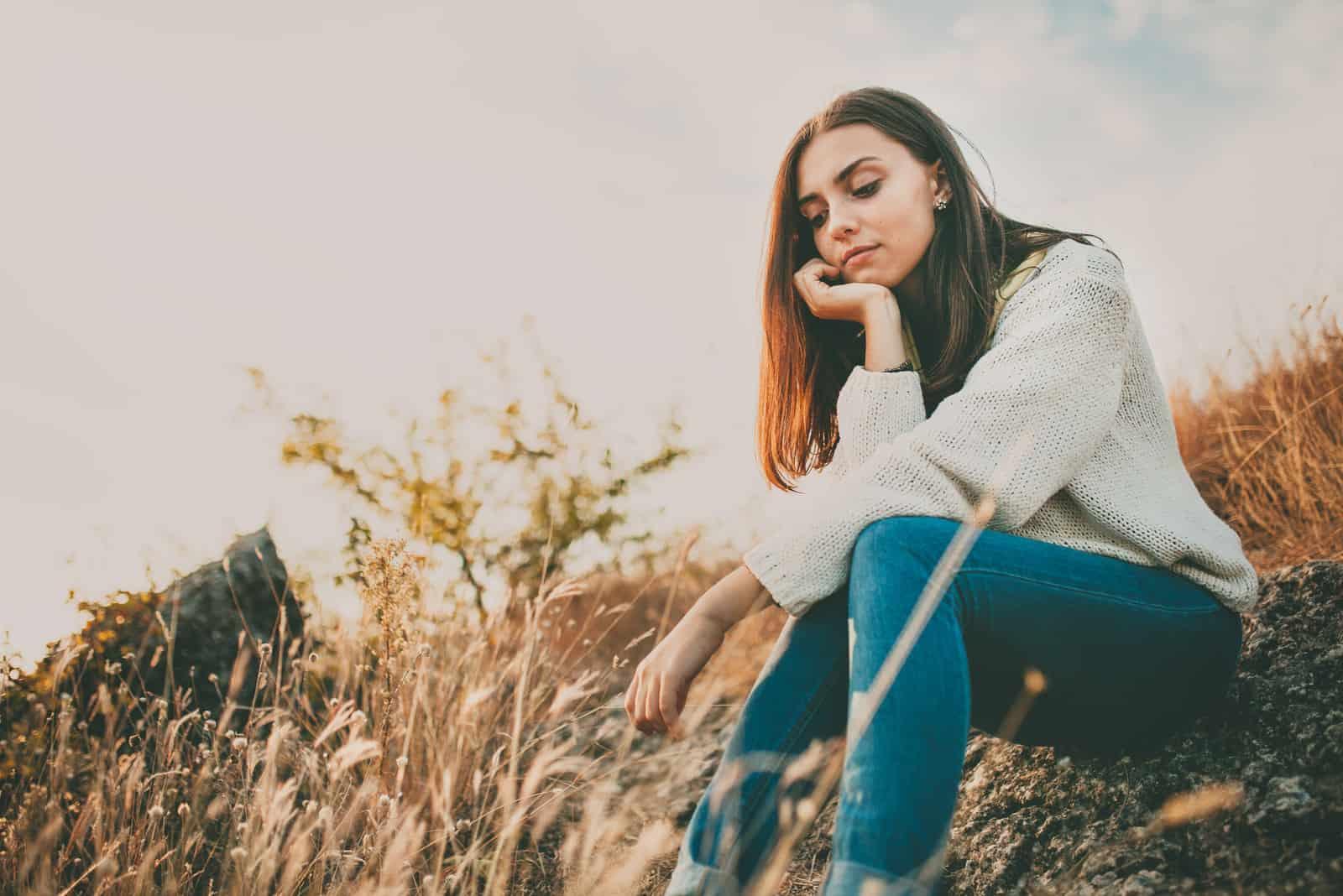 la femme est assise pensivement sur l'herbe