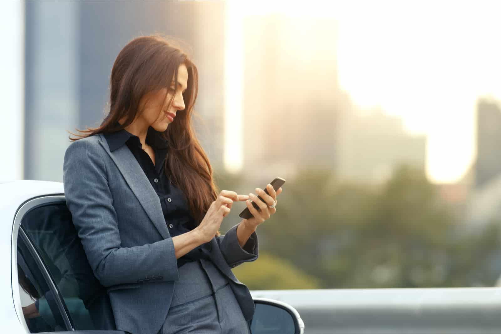 la femme est debout près de la voiture et le bouton du téléphone