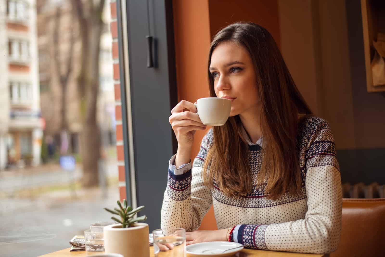 la femme s'assoit et boit du café