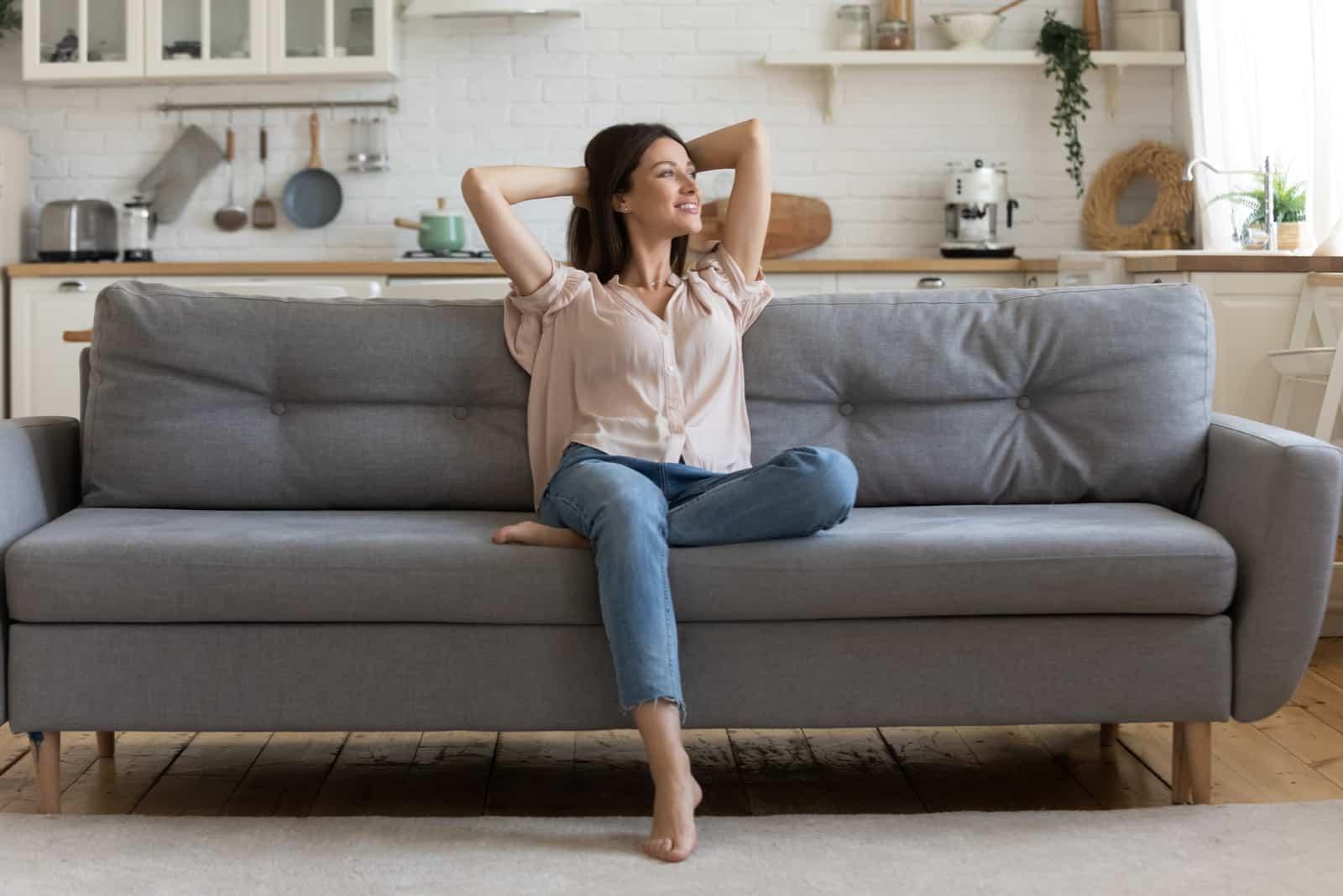 la femme s'assoit sur le canapé et rit