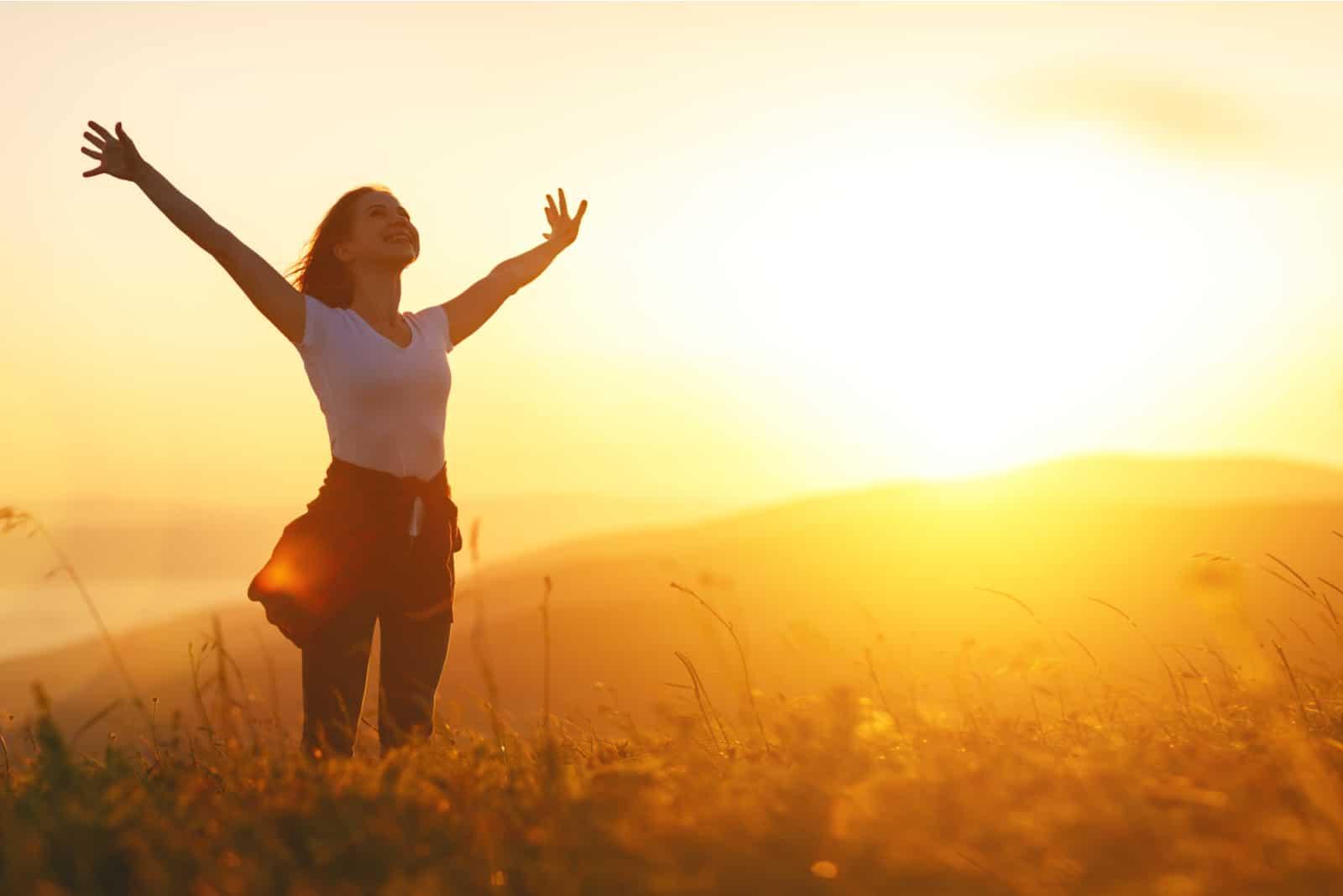 la femme se tient les bras tendus dans le champ