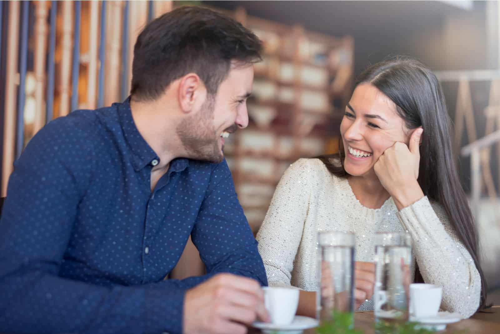 l'homme et la femme s'assoient en se regardant et en riant
