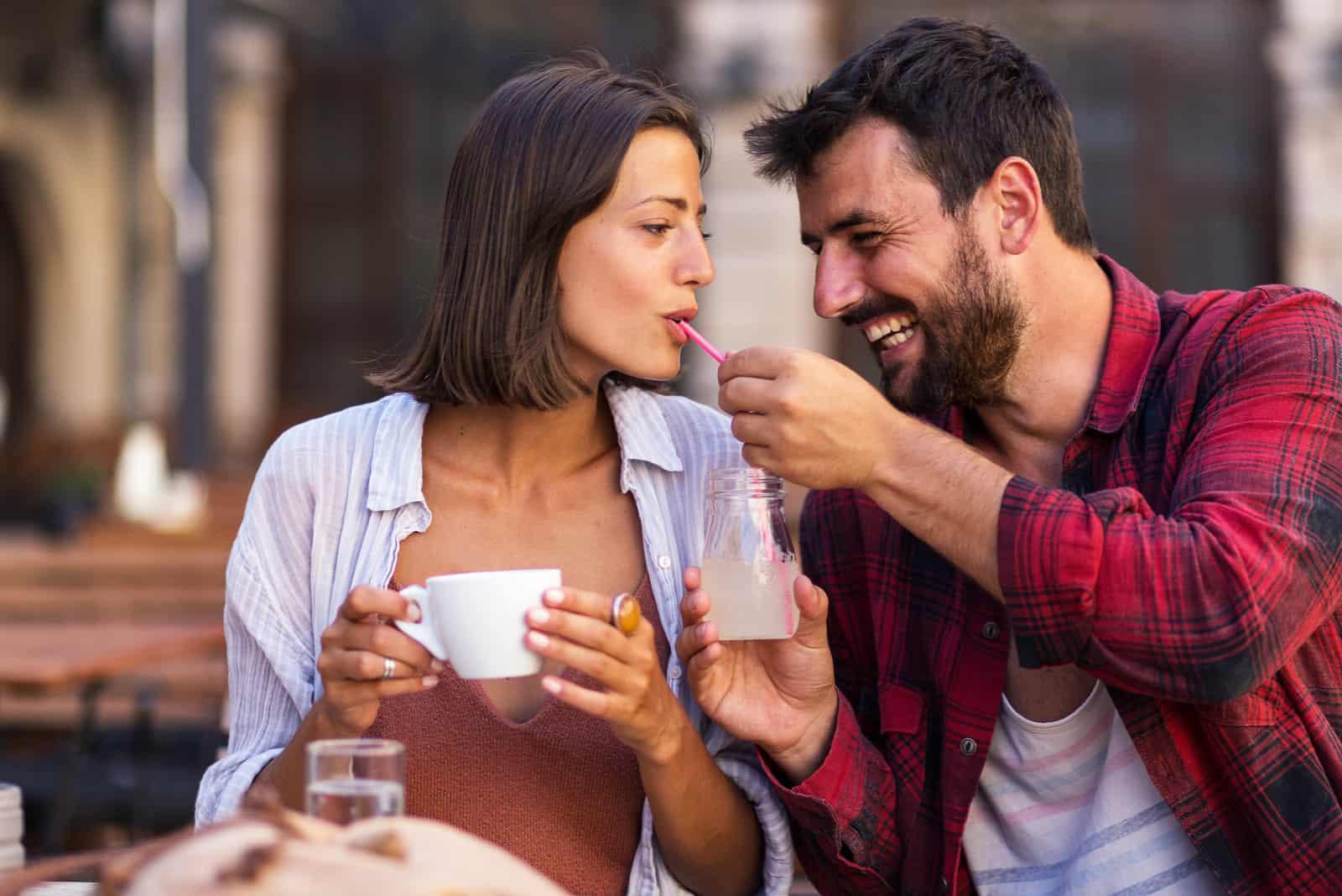 l'homme rit en donnant à la femme le jus à boire à une paille