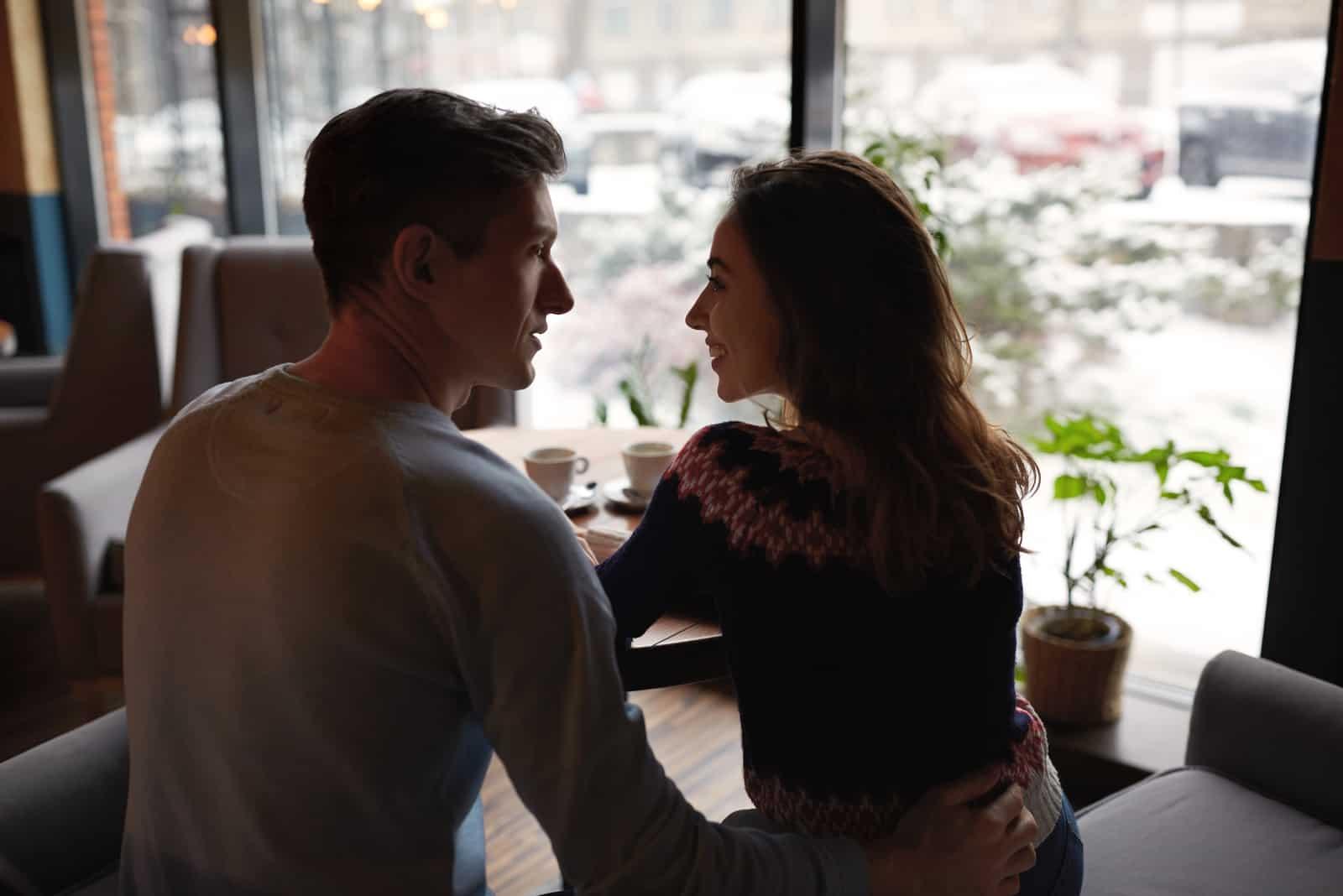 l'homme serra la femme dans ses bras alors qu'ils étaient assis