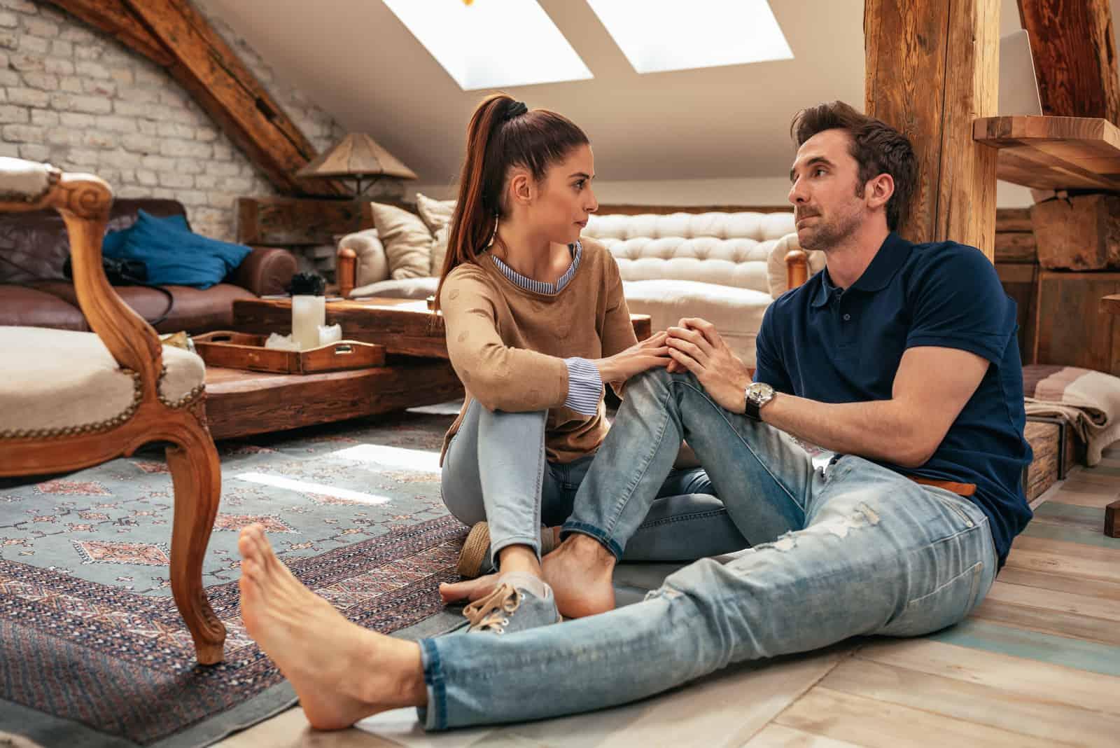 séduisant jeune couple parlant dans le salon