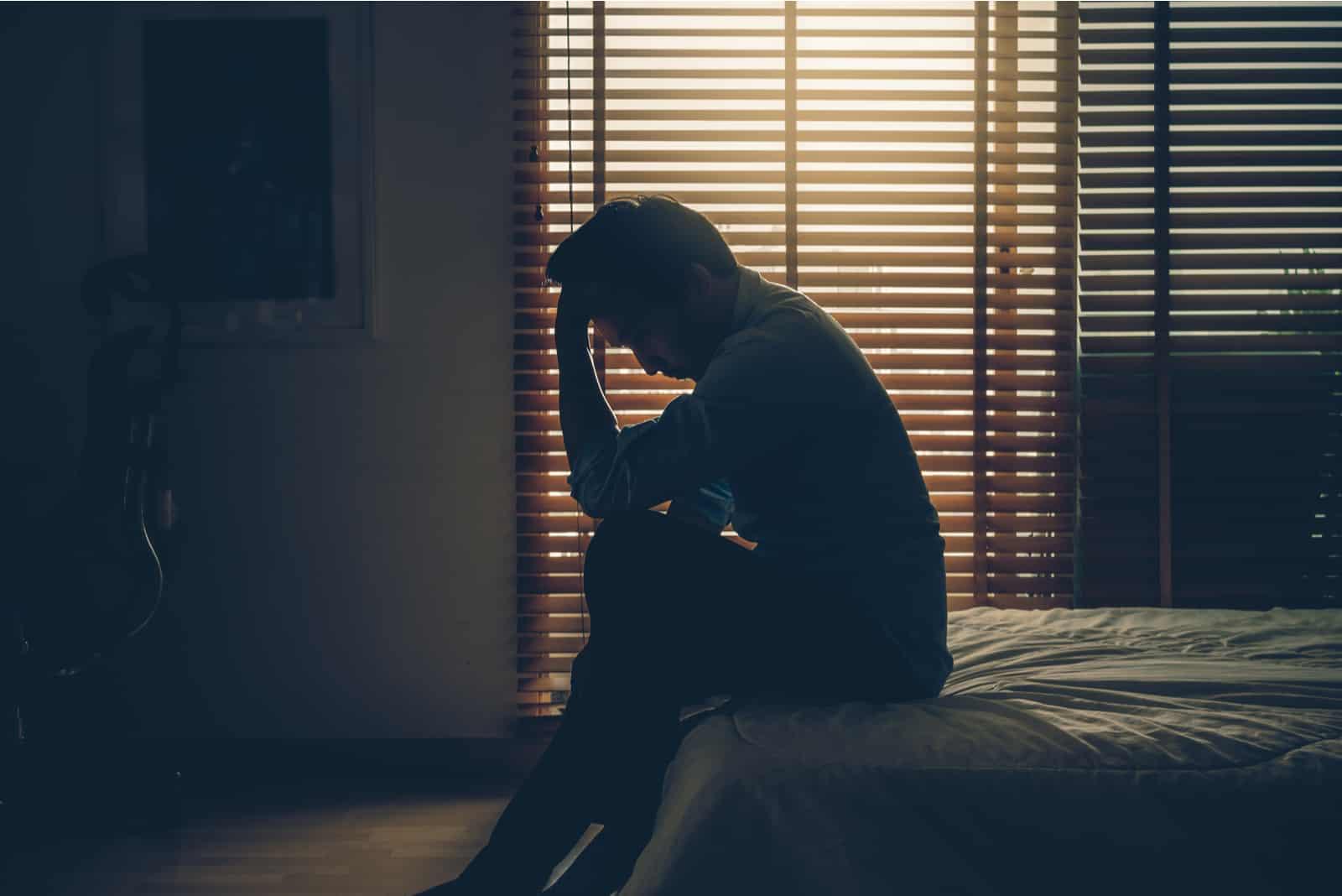 un homme assis sur un lit