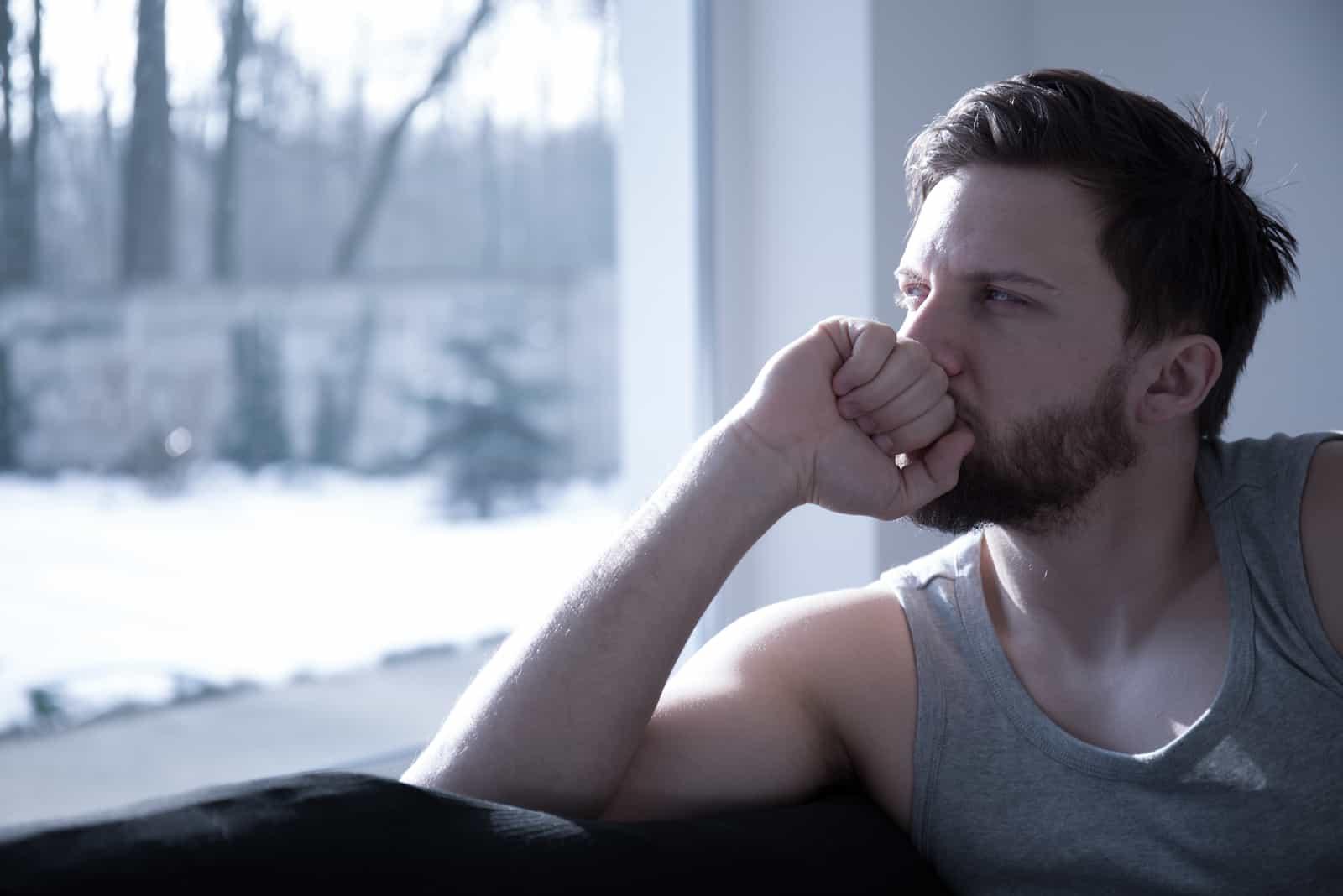 un homme est assis pensivement près de la fenêtre