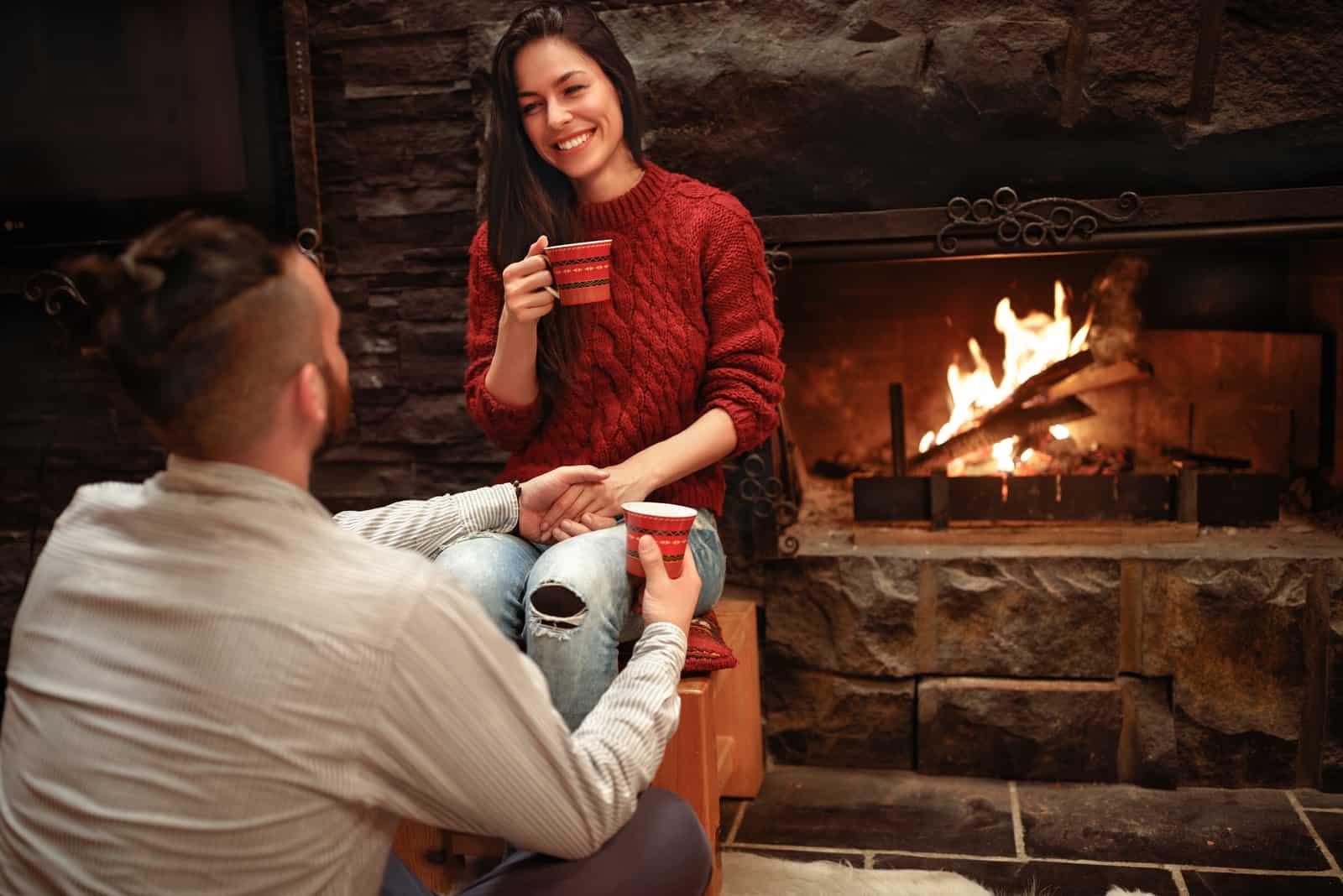 un homme et une femme assis près de la cheminée rient en buvant du café et se tenant la main