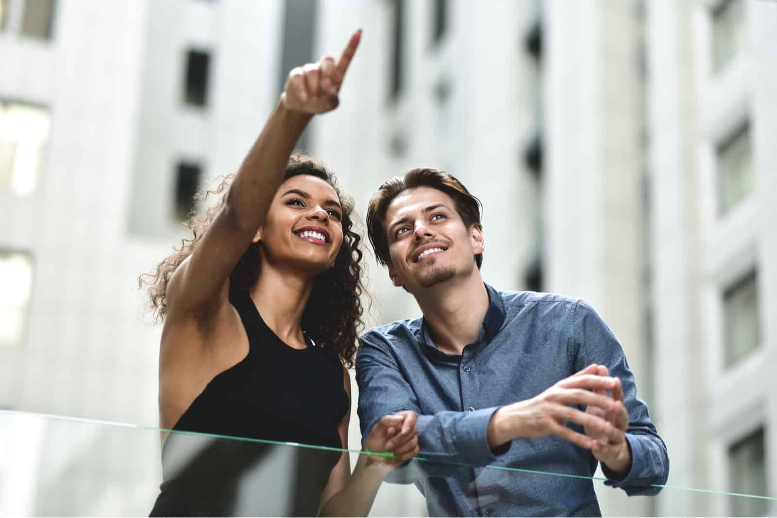 un homme et une femme debout, elle lui montre quelque chose