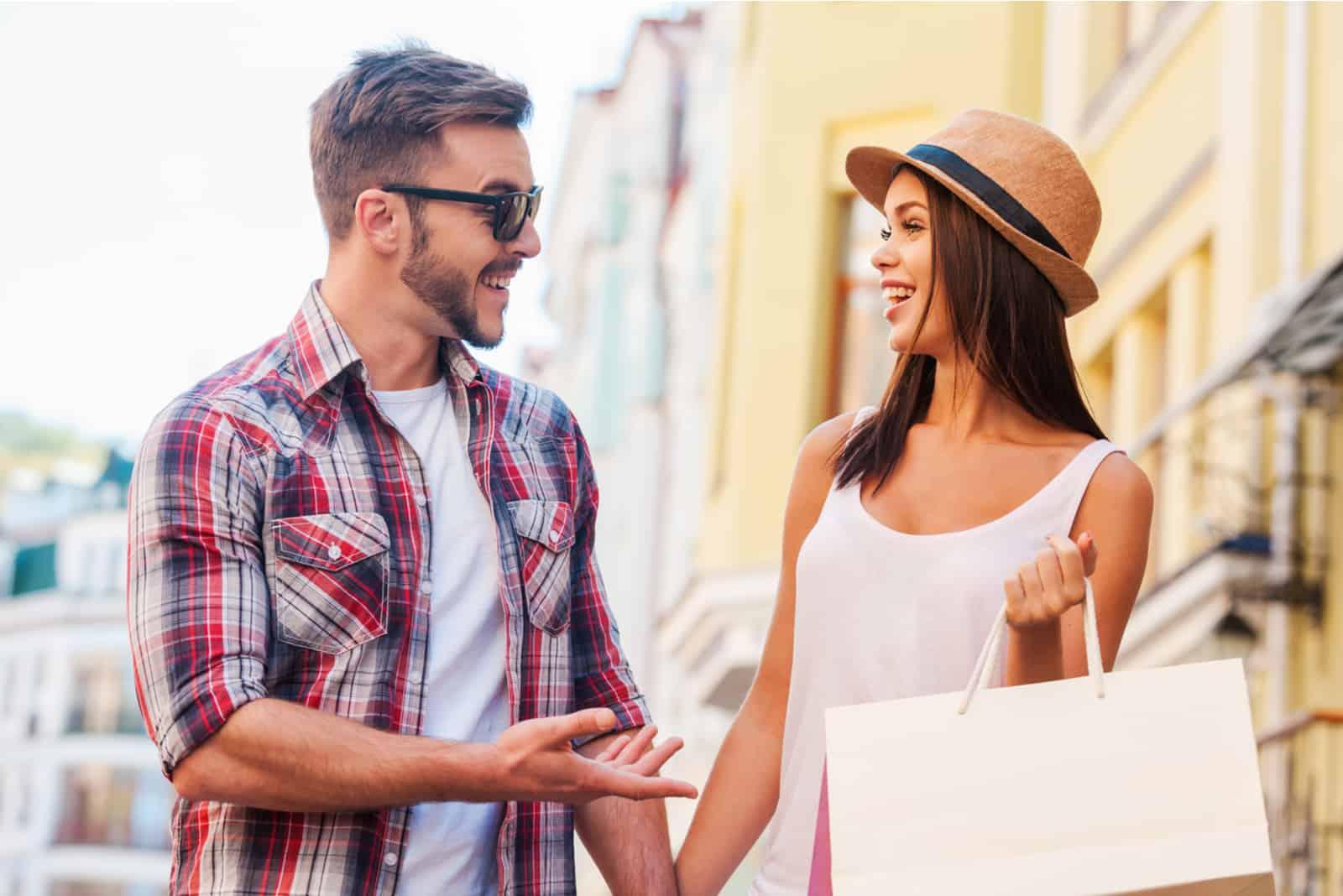 un homme et une femme marchent dans la rue et rient