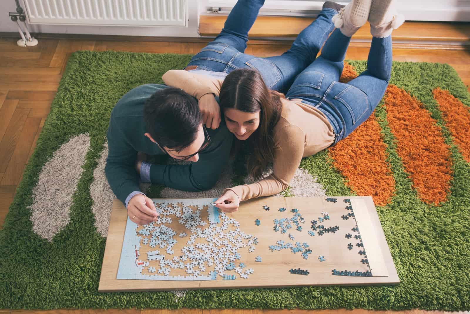 un homme et une femme s'allongent sur le lit et assemblent des puzzles