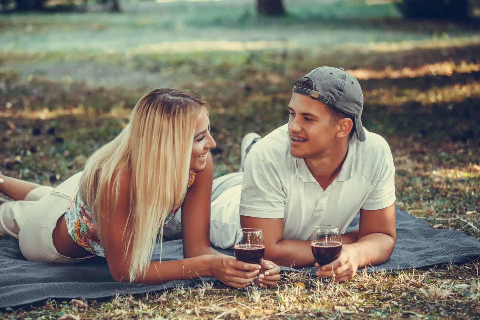un homme et une femme s'allongent sur l'herbe et boivent du vin
