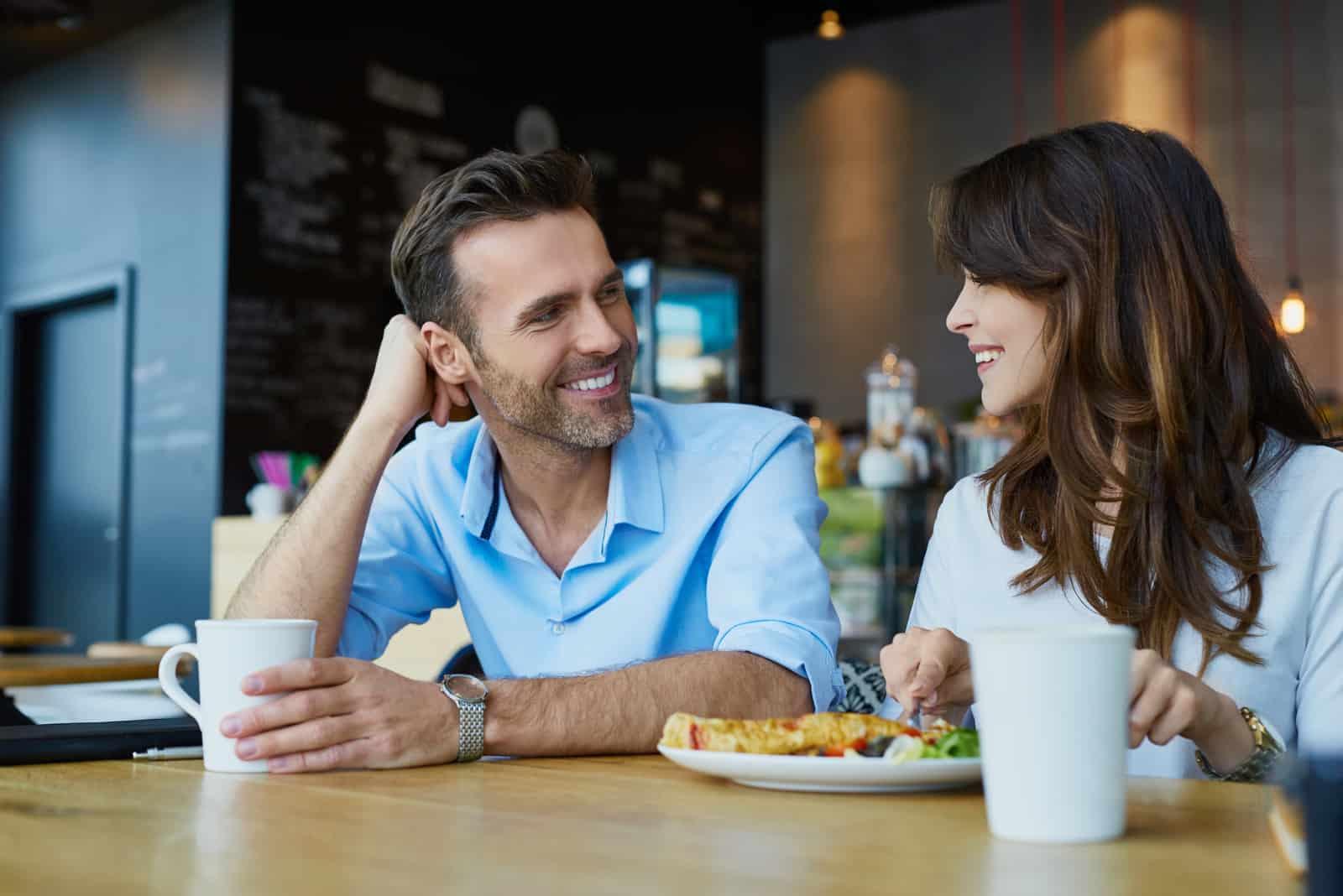 un homme et une femme s'assoient à une table et se regardent et rient