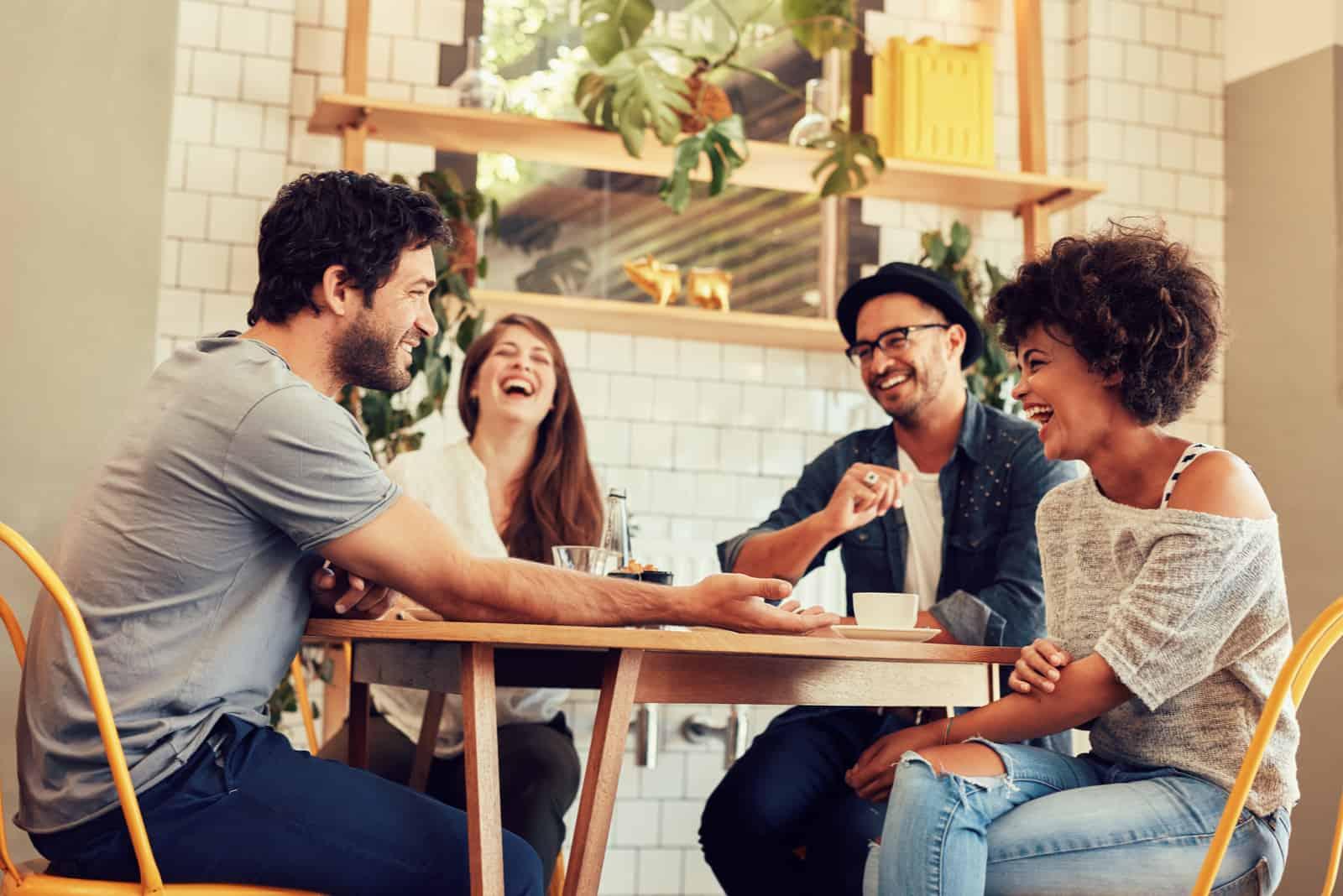 un homme et une femme s'assoient avec des amis et rient