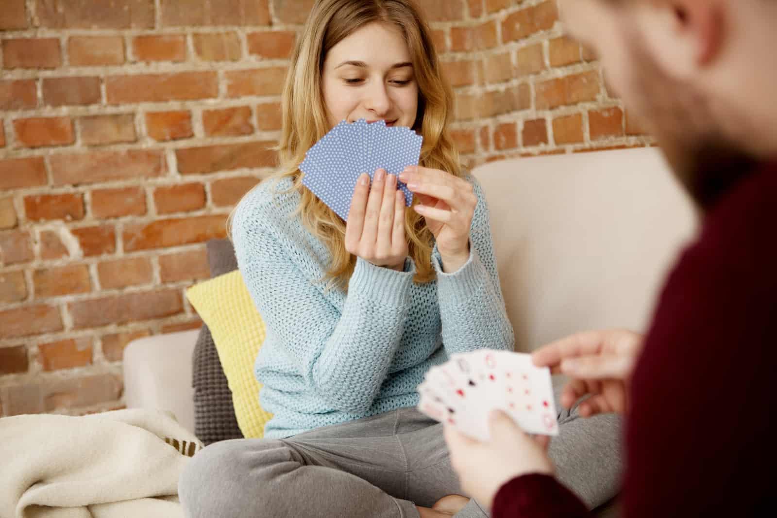 un homme et une femme s'assoient et jouent aux cartes