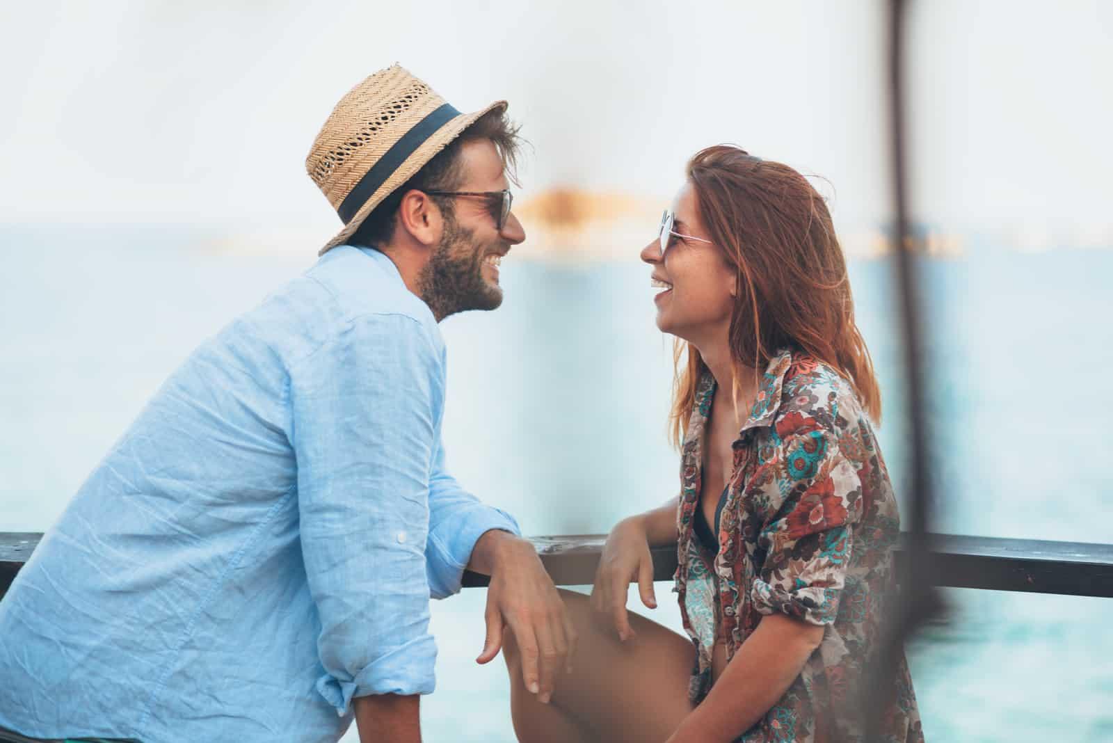 un homme et une femme s'assoient l'un à côté de l'autre et rient