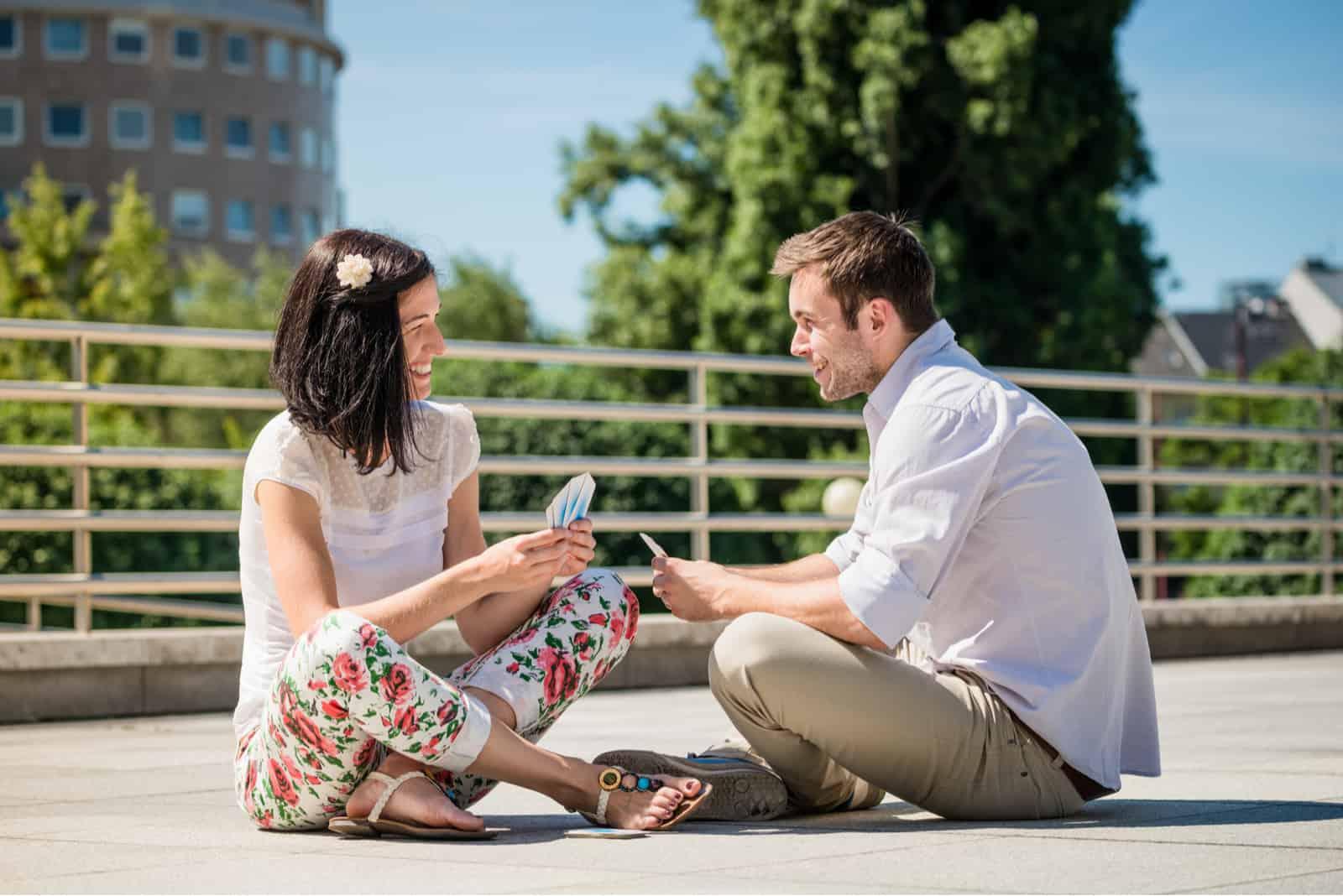 un homme et une femme s'assoient sur le béton et jouent aux cartes