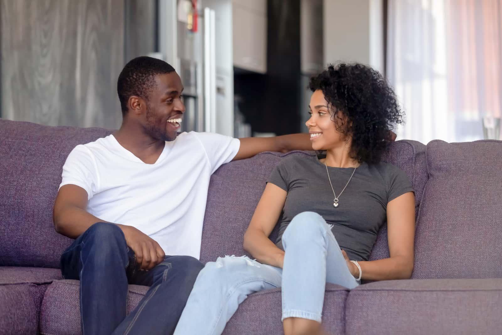 un homme et une femme s'assoient sur le canapé et rient