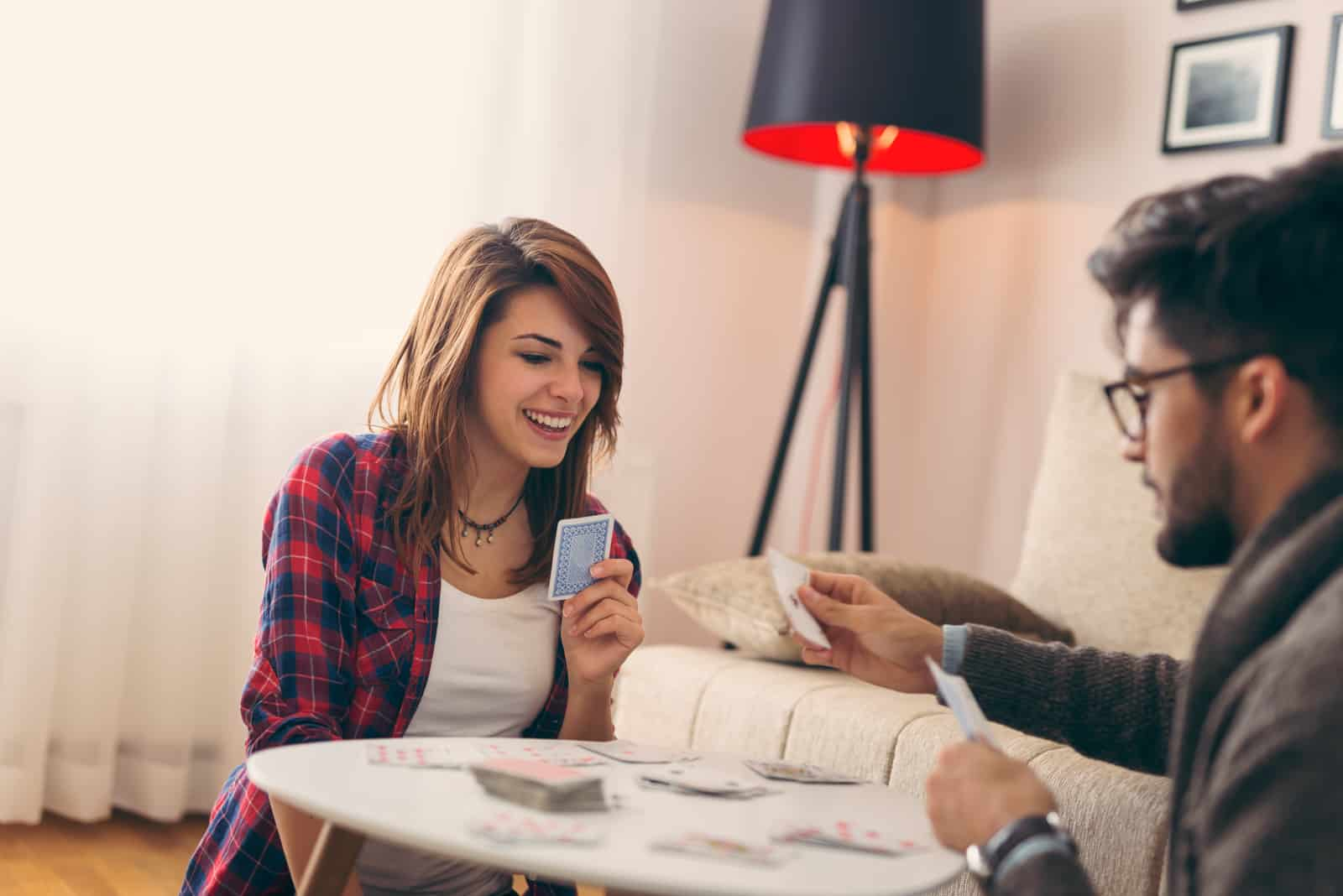 un homme et une femme s'assoient sur le sol et jouent aux cartes sur la table