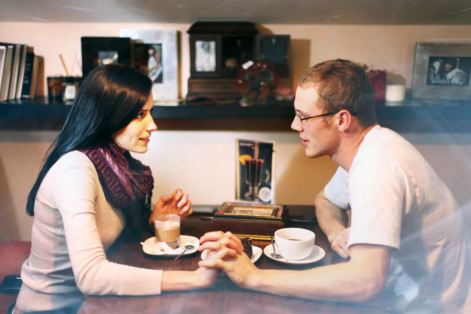 un homme et une femme se tenant la main en buvant du café