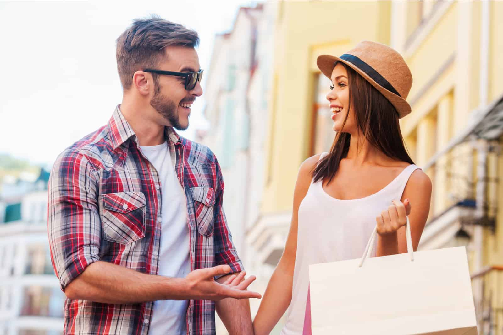 un homme et une femme se tiennent dans la rue et rient