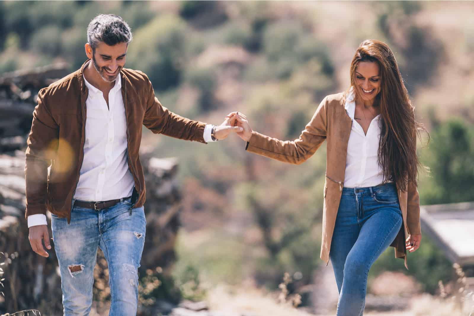 un homme et une femme se tiennent la main et marchent