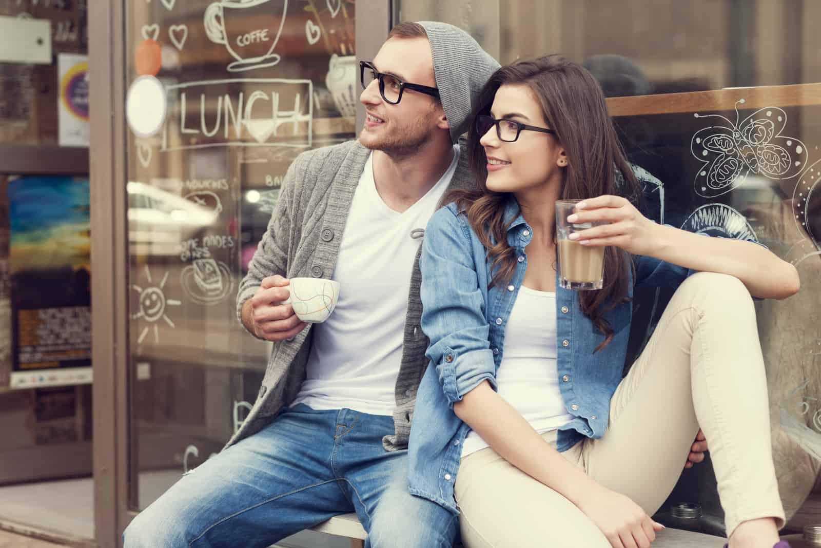 un homme et une femme sont assis à boire du café et à regarder