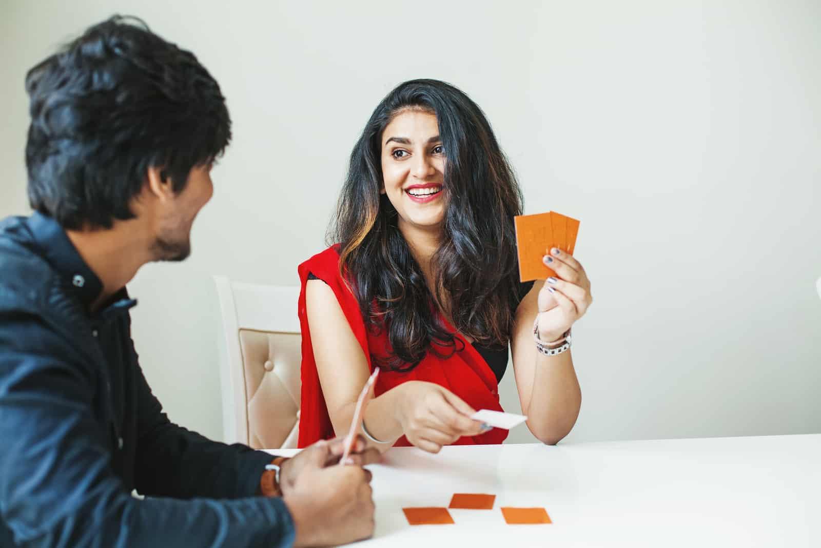 un homme et une femme sont assis à une table et jouent aux cartes