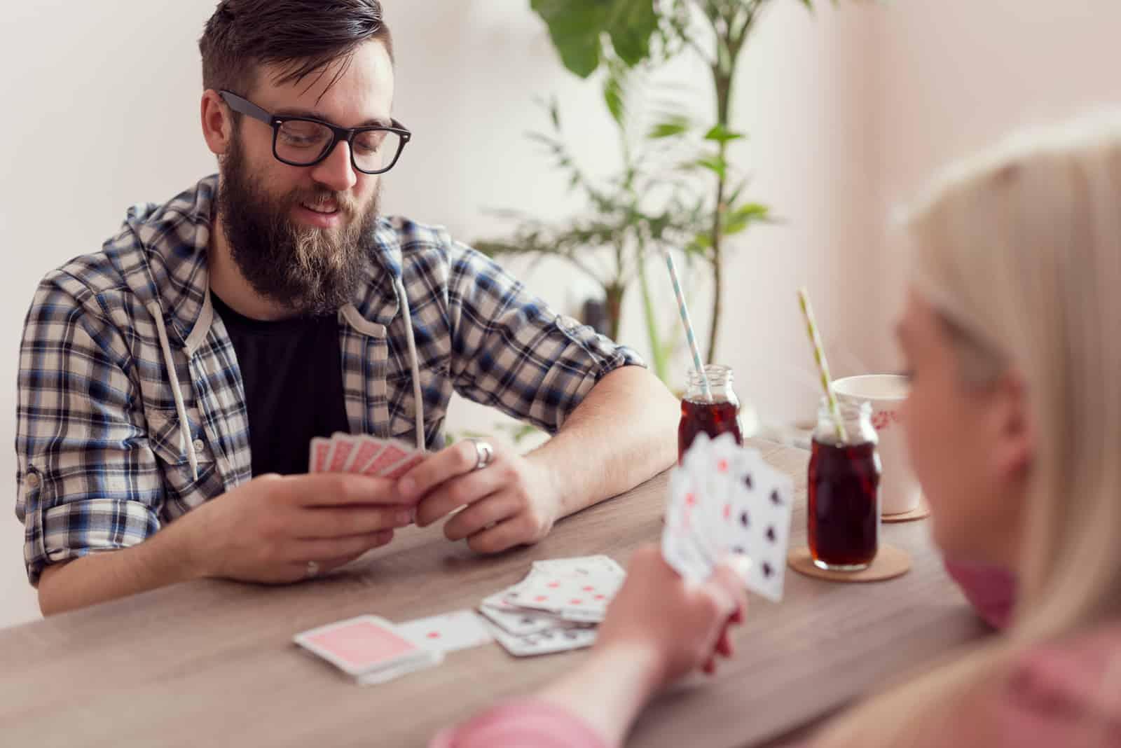 un homme et une femme sont assis à une table face à face et jouent aux cartes