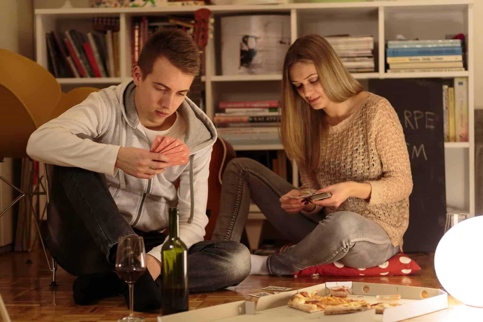 un homme et une femme sont assis sur le sol et jouent aux cartes