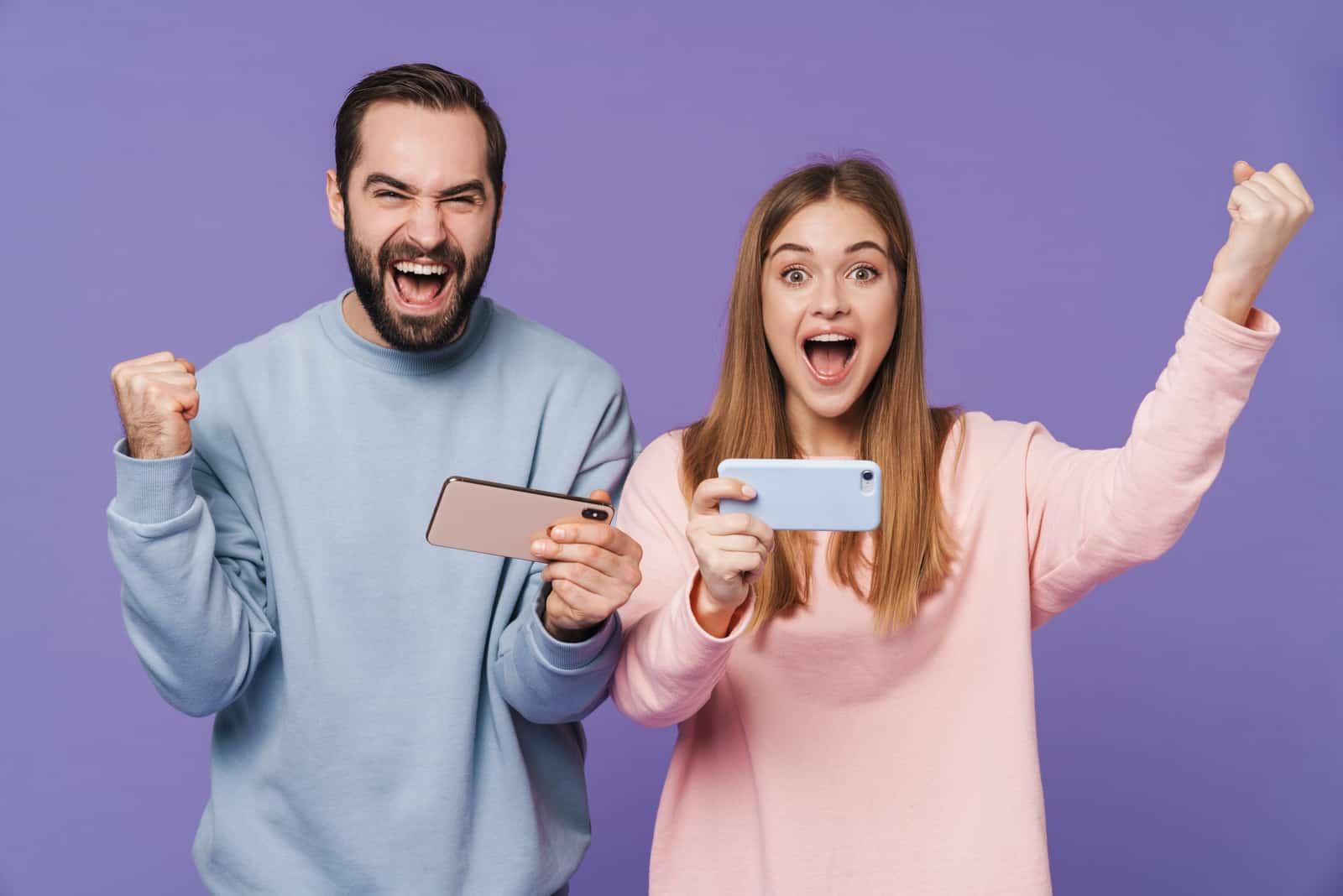 un homme et une femme tiennent un téléphone dans leurs mains