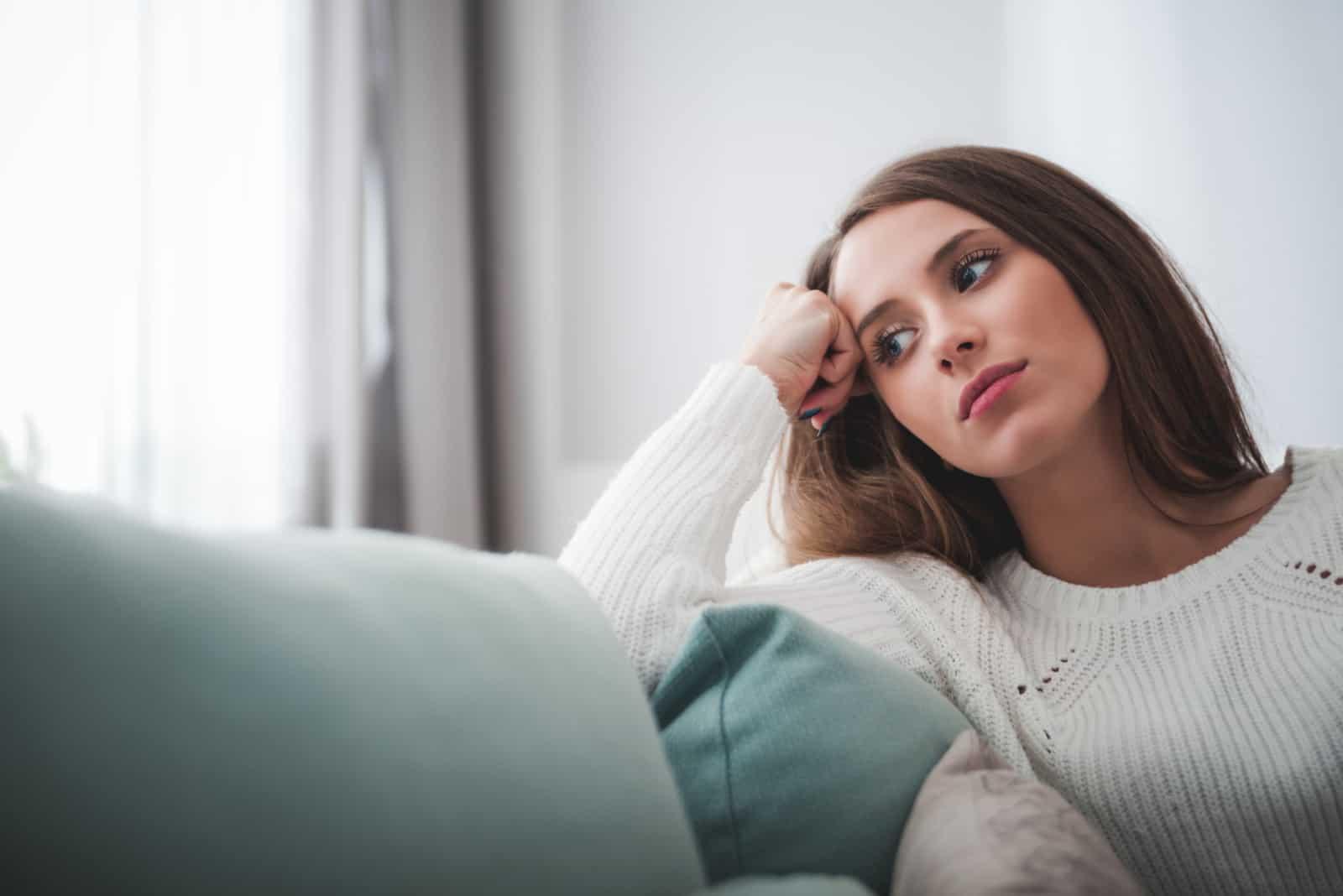 une femme assise à la maison et plongée dans ses pensées