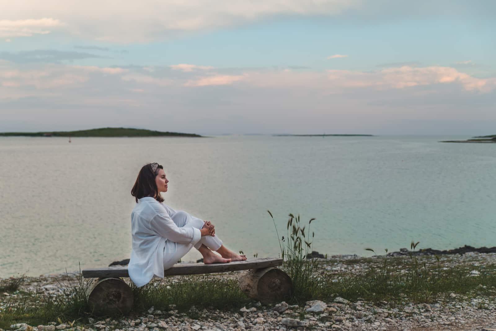 une femme assise au bord de la mer