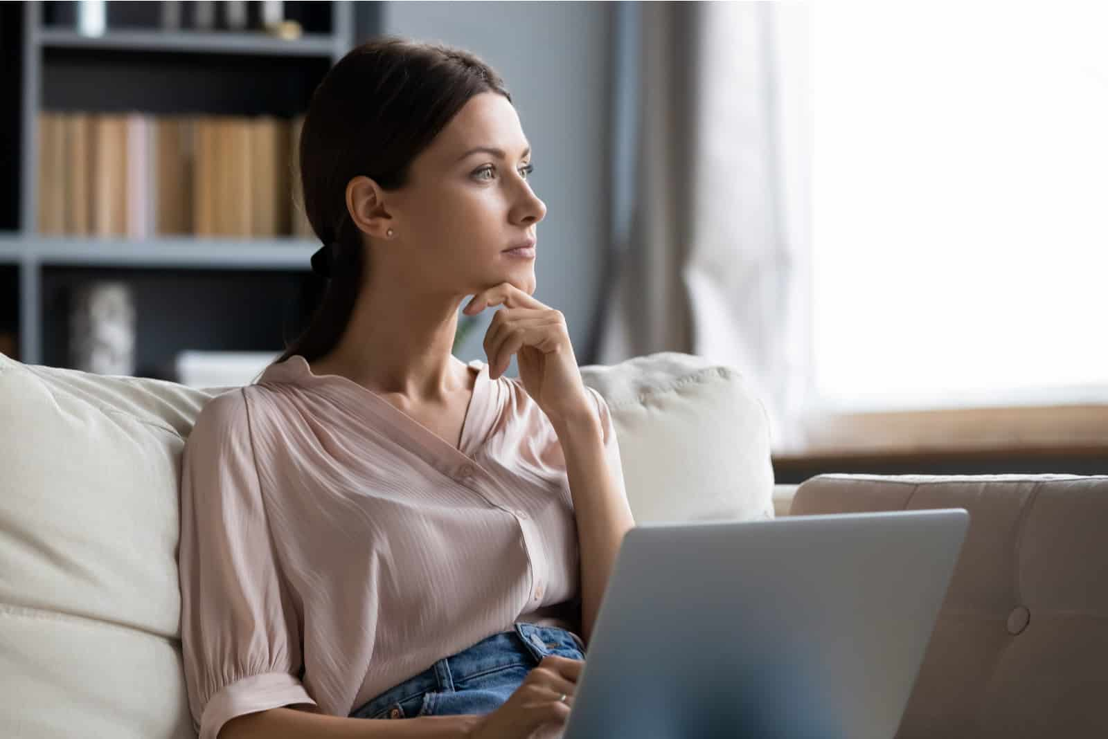 une femme assise devant un ordinateur portable pensivement