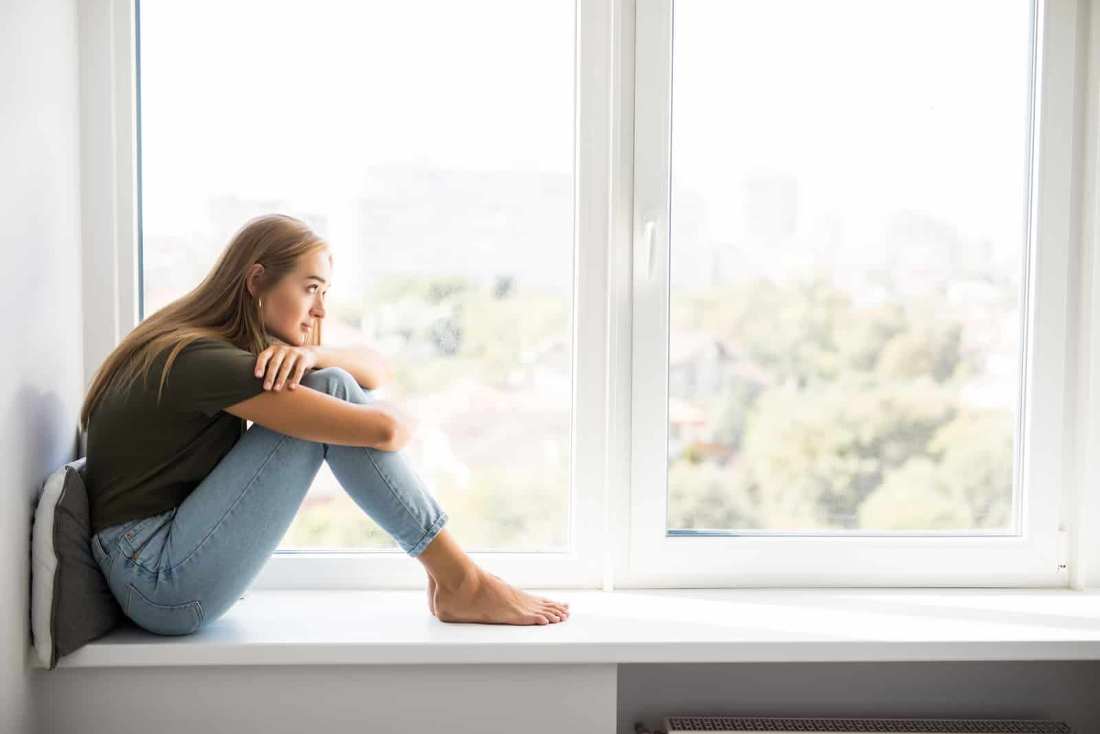 une femme assise près de la fenêtre