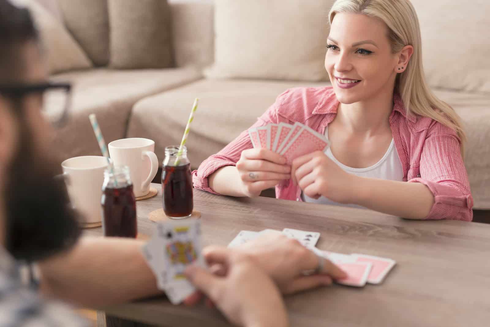 une femme assise sur le sol et jouer aux cartes avec un homme