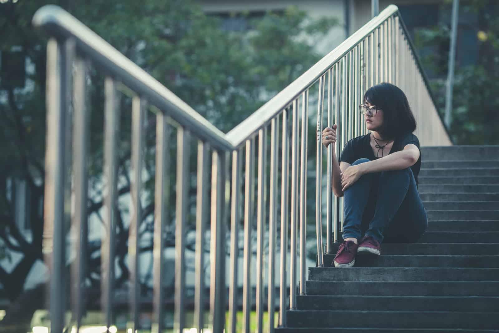 une femme assise sur les escaliers